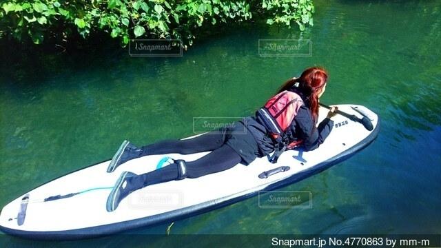 水の上にボードで浮かび寝ころぶ女性の写真・画像素材[4770863]
