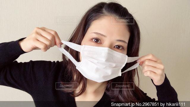 マスクをつけようとしている女性の写真・画像素材[2967851]