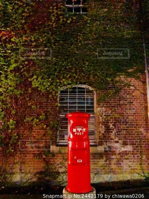 レンガ造りの建物の前にある赤い郵便ポストの写真・画像素材[2442179]