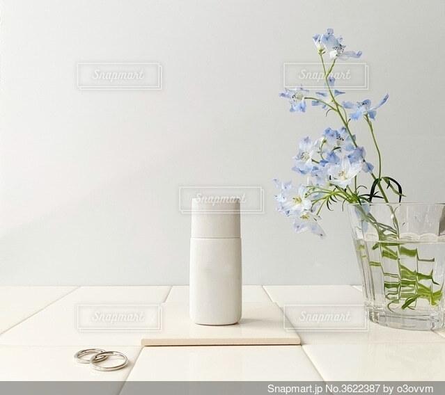 テーブルの上に花の花瓶とボトルの写真・画像素材[3622387]