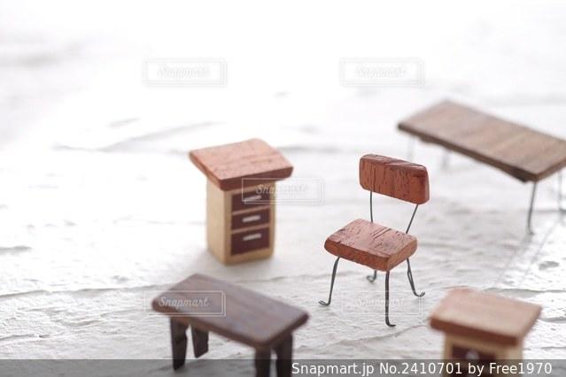 白い背景の上に置いたミニチュアの椅子や机や棚の模型の写真・画像素材[2410701]
