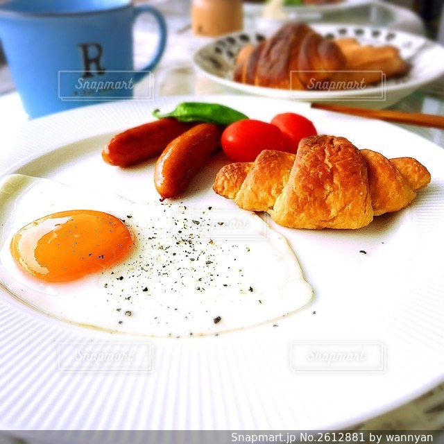 クロワッサン、目玉焼き、ソーセージの朝食の写真・画像素材[2612881]