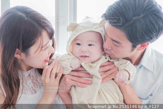 赤ん坊を抱いている夫婦の写真・画像素材[2535146]