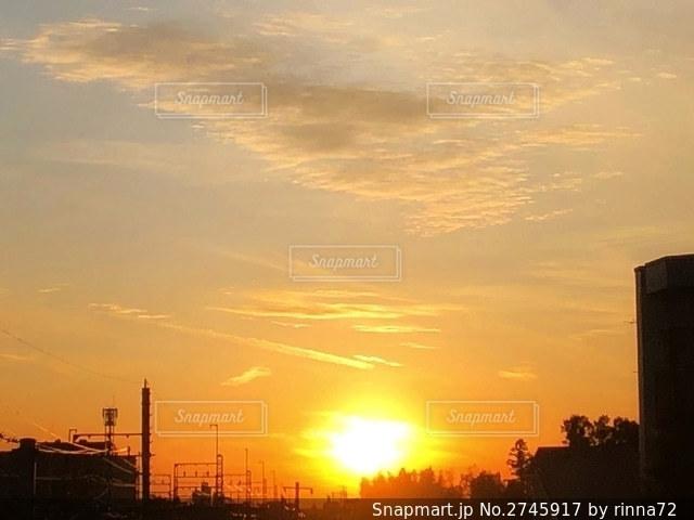 淡いオレンジ色の空と街に沈む滲んだ夕日のある風景の写真・画像素材[2745917]