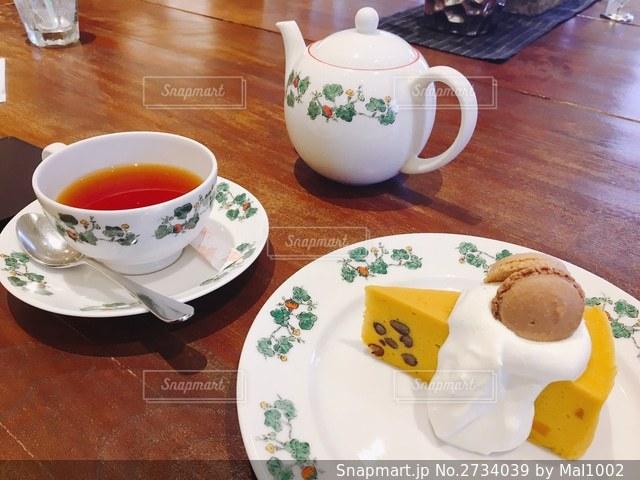 テーブルの上のティーセットとマカロン付きケーキの写真・画像素材[2734039]