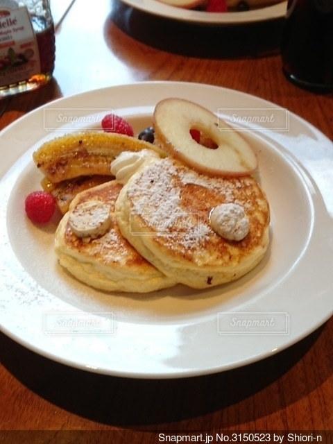 食べ物の皿をテーブルの上に置くの写真・画像素材[3150523]