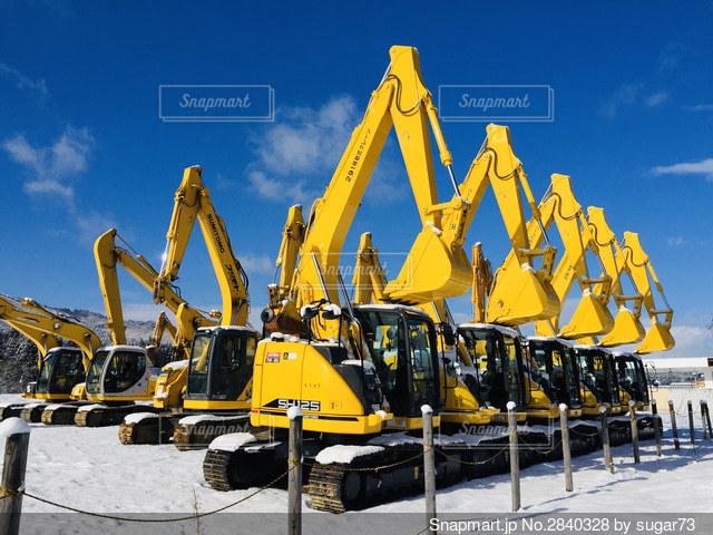 雪景色にたたずむ大きな黄色い機械の写真・画像素材[2840328]