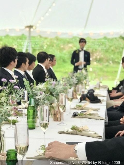 緑豊かな屋外で行われた結婚式の様子。焦点加工で人物が判別されないようにしています。の写真・画像素材[3473454]