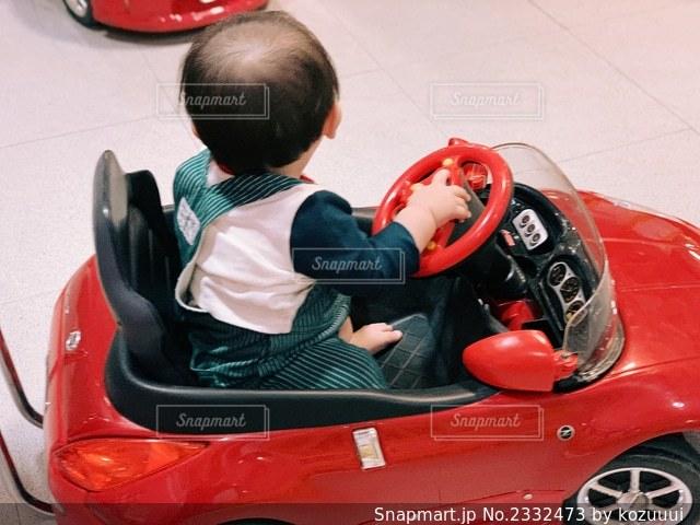 赤い車に座っている小さな子供の写真・画像素材[2332473]