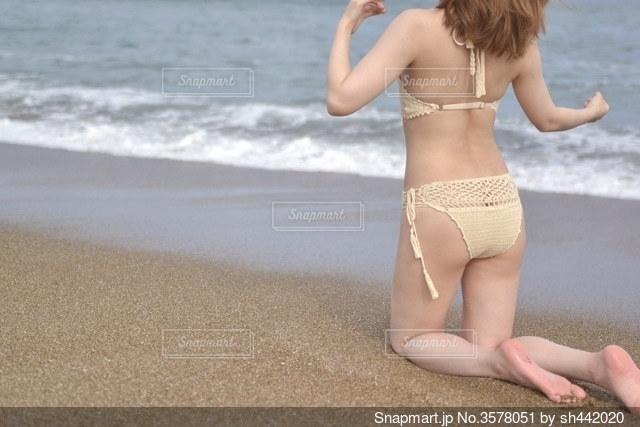 波打ち際でポーズをとる水着女性の写真・画像素材[3578051]