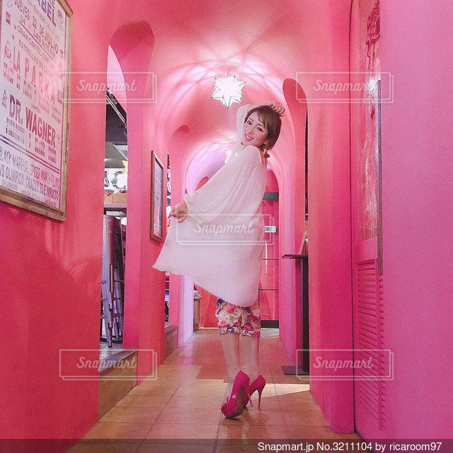 ピンクのカフェで振り向く女の子の写真・画像素材[3211104]