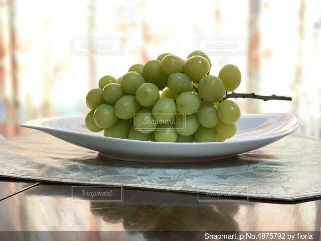 木製のテーブルの上に座っている果物のボウルの写真・画像素材[4875792]