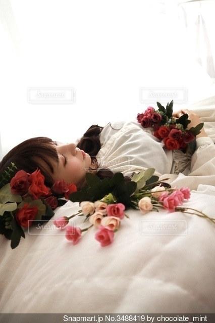 ベッドの上に横たわっている花と女性の写真・画像素材[3488419]