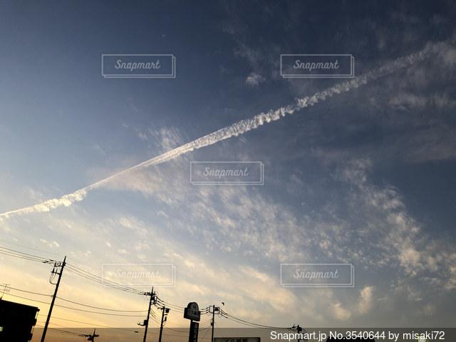 夕焼け空と飛行機雲の写真・画像素材[3540644]
