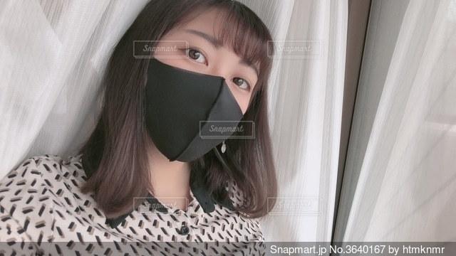 黒マスクをつけてカメラを見ている女性の写真・画像素材[3640167]