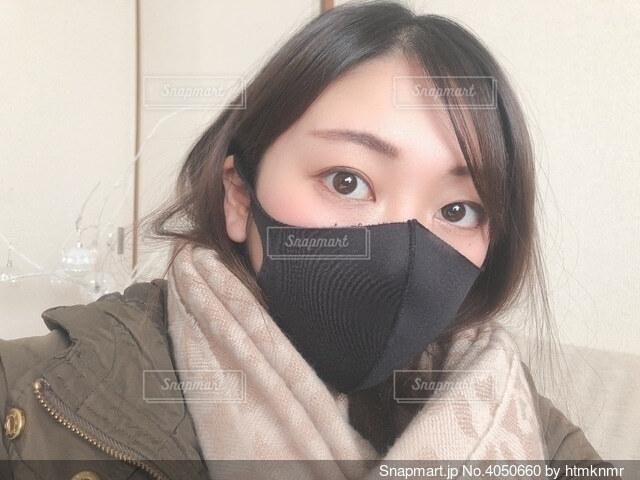 黒マスクでカメラを見る女性の写真・画像素材[4050660]