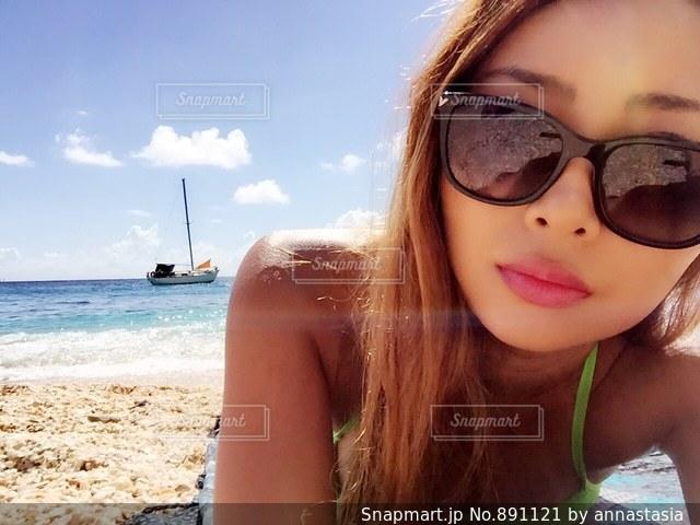 近くにビーチで座っているサングラスの女性のアップの写真・画像素材[891121]