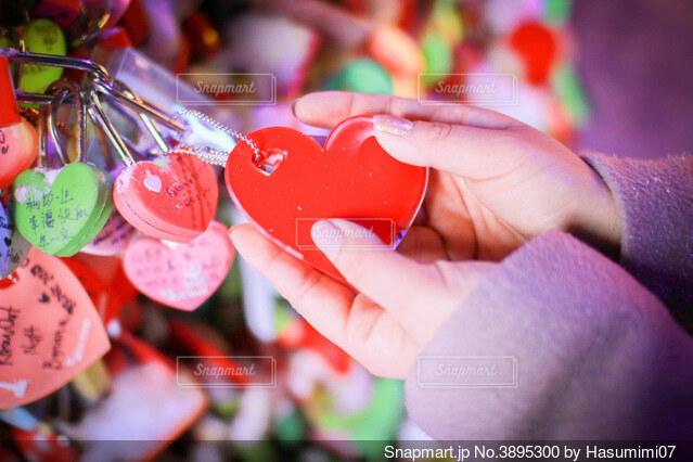 縁結びの赤いハートと手の写真・画像素材[3895300]