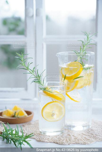 テーブルの上の花瓶の横にオレンジジュースのグラスの写真・画像素材[4319626]