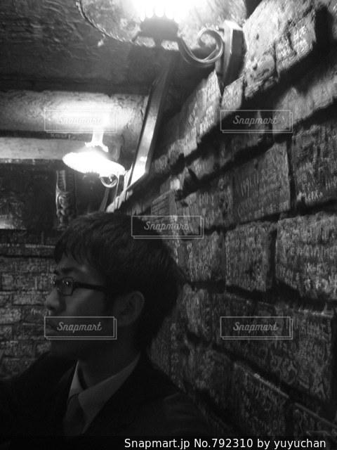 レンガ壁の前に立っている男の写真・画像素材[792310]