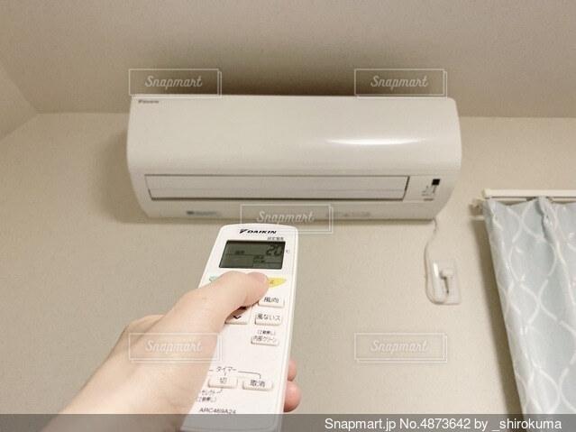 エアコンのリモコンを持つ手の写真・画像素材[4873642]