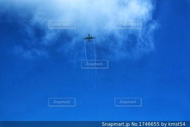 青い空を飛んでいる飛行機の写真・画像素材[1746655]