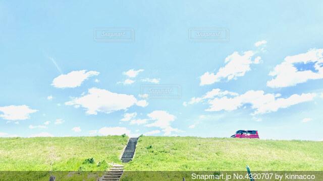 晴れた堤防を走る赤い車の写真・画像素材[4320707]