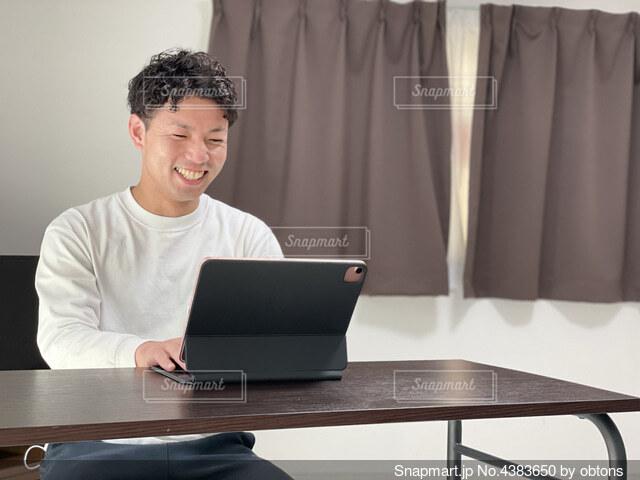 ラップトップコンピュータを使ってテーブルに座っている人の写真・画像素材[4383650]