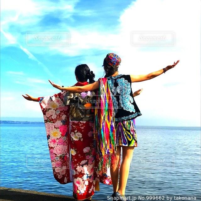 水の体の横に立っている人のグループの写真・画像素材[999662]