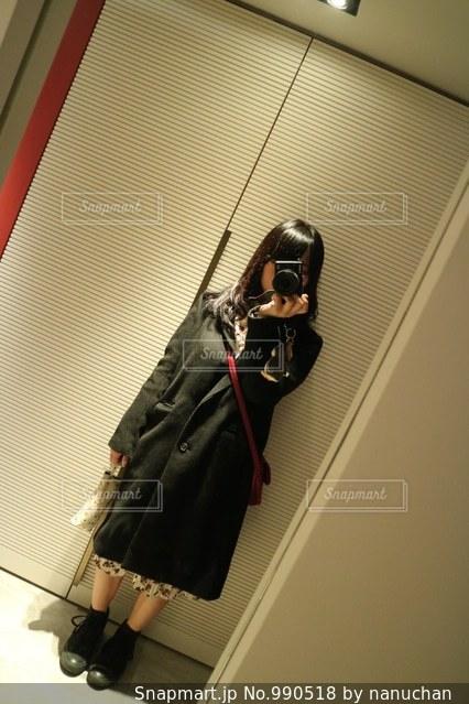 カメラにポーズ鏡の前に立っている人の写真・画像素材[990518]