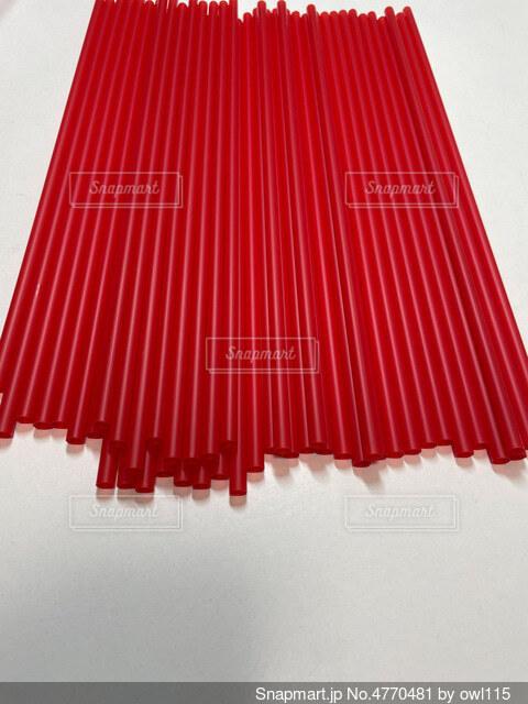 白いテーブルの上に赤いストローの写真・画像素材[4770481]