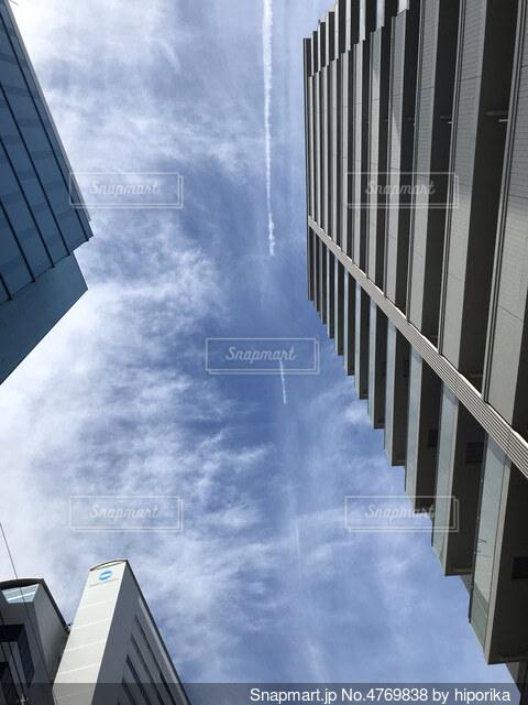 ビルの間から見える飛行機雲の写真・画像素材[4769838]