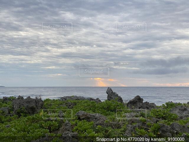水の体の隣の岩場のビーチで人々のグループの写真・画像素材[4770020]