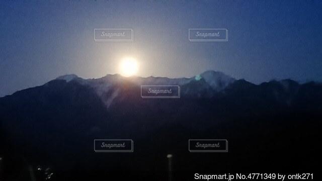 雪化粧した駒ヶ岳かから出る月の写真・画像素材[4771349]