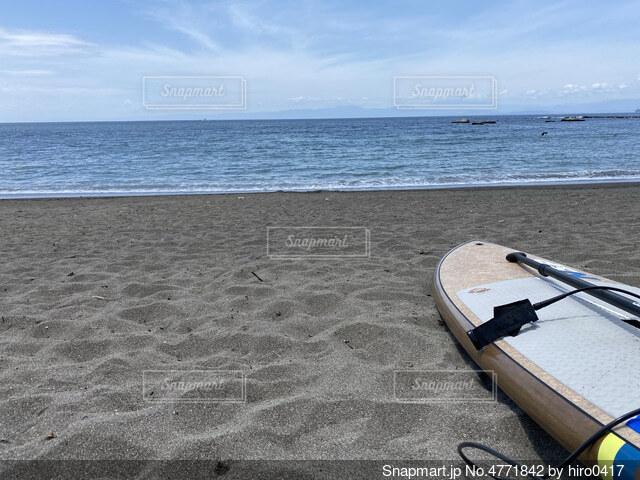 海の隣の砂浜の上に座っているボートの写真・画像素材[4771842]