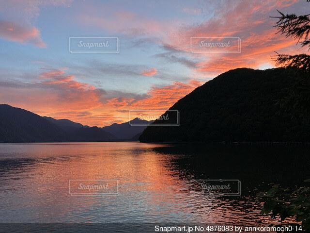 山を背景にした水の体に沈む夕日の写真・画像素材[4876083]