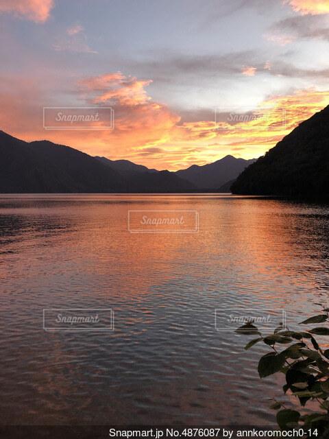 山を背景にした水の体に沈む夕日の写真・画像素材[4876087]