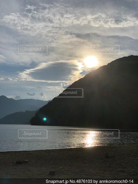背景に山のある水の体の写真・画像素材[4876103]