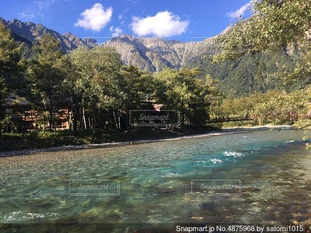 背景に山のある水の体の写真・画像素材[4875968]