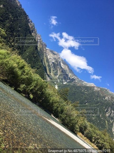 山の側に木がある道の写真・画像素材[4875975]