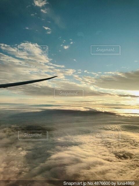 雲の上を飛ぶ飛行機の写真・画像素材[4876600]