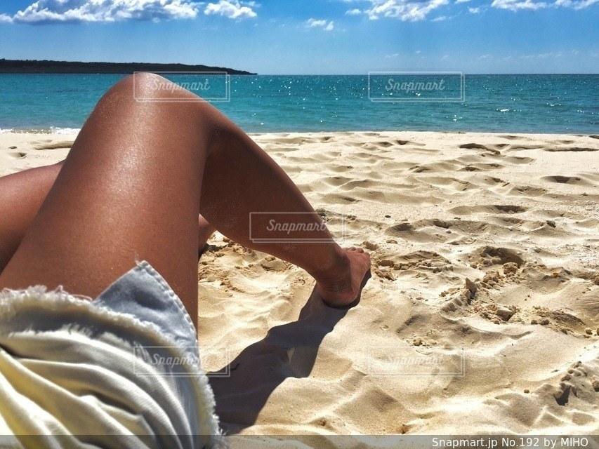 砂浜で座っている女性の写真・画像素材[192]