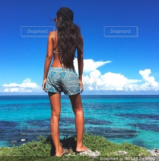 水の体の横に立っている人の写真・画像素材[149]