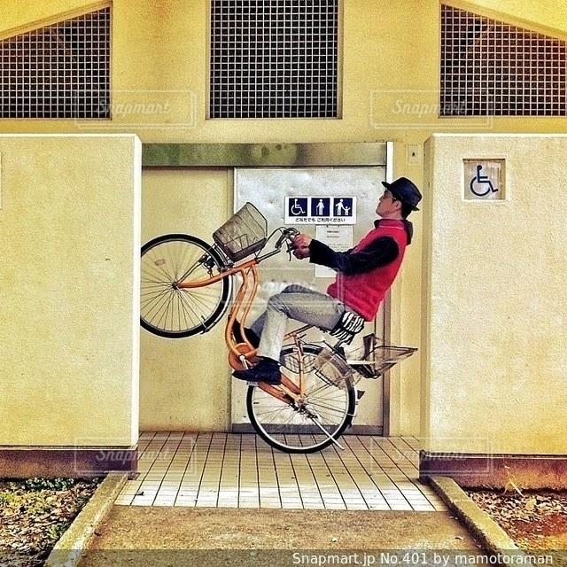 建物の前に自転車を持つ男 - No.401