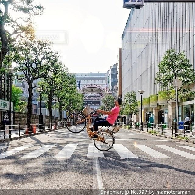建物の前で自転車に乗る男 - No.397