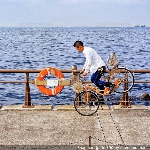 水の体の前で自転車を持つ男 - No.390