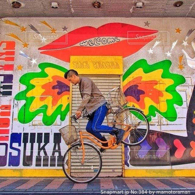 覆われている落書きの壁の横に立っている人の写真・画像素材[384]