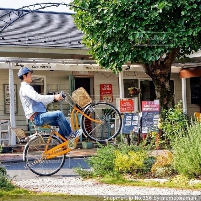 建物の前に自転車を持つ男 - No.356