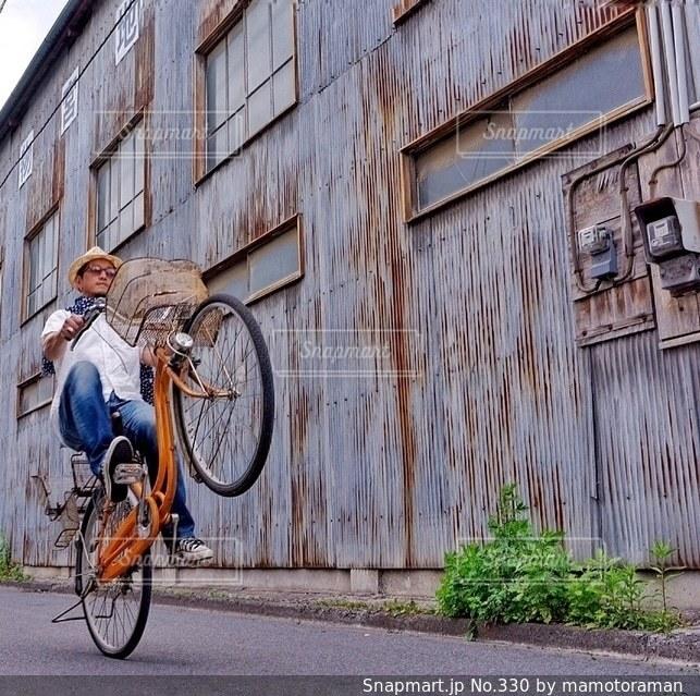 建物の前で自転車に乗る男の写真・画像素材[330]