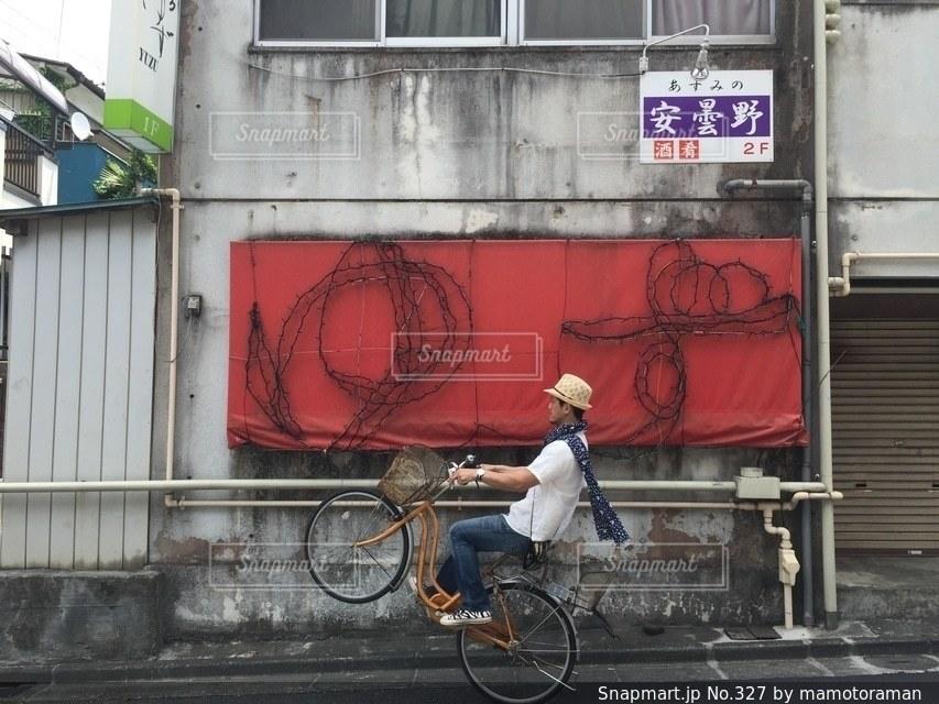 建物の前で自転車に乗る男 - No.327